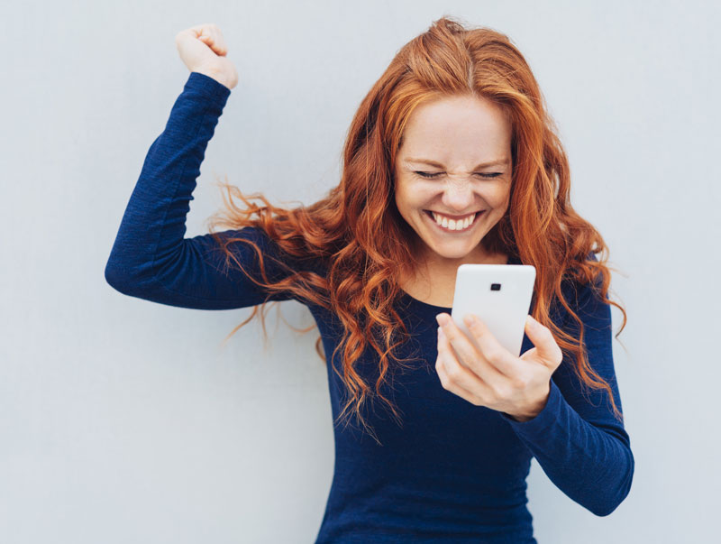 young woman excited using a phone